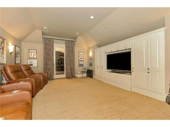 Media room with brown leather recliners and a TV fitted on the white built-in cabinet.