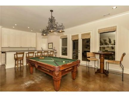 Game room with a sitting area, wet bar, and billiards table lit by an ornate chandelier.