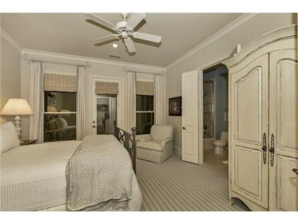 Another bedroom with a comfy bed, gray armchair, and a distressed wardrobe over carpet flooring.