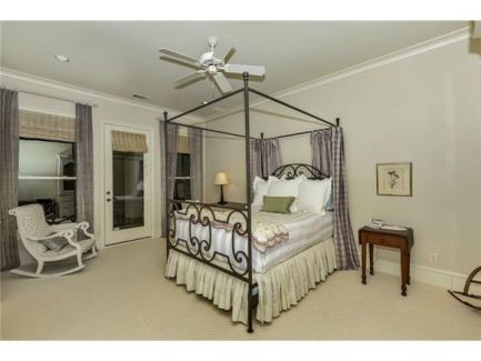 This bedroom offers a rocking chair and a canopy bed flanked by wooden nightstands.