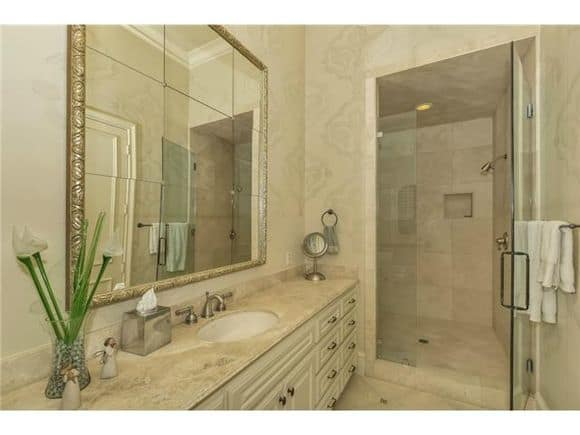 Bathroom with a walk-in shower and a lengthy vanity paired with a large paneled mirror.