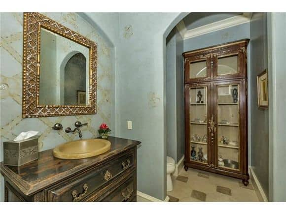 This bathroom has a display cabinet, a wooden vanity and a toilet concealed behind the archway.