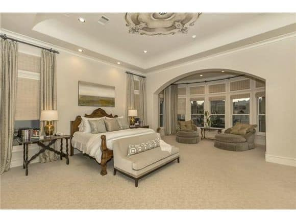 Primary suite with a stunning tray ceiling and an open archway that defines the sitting area.