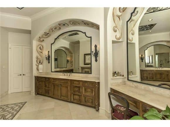The master bathroom offers two large vanities paired with arched mirrors.
