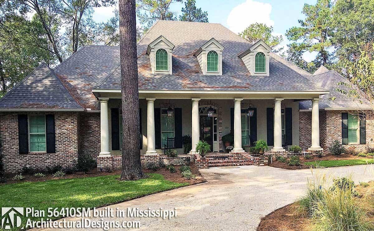 Home's facade shows the brock cladding, charming dormer windows, and white exterior columns framing the front porch.