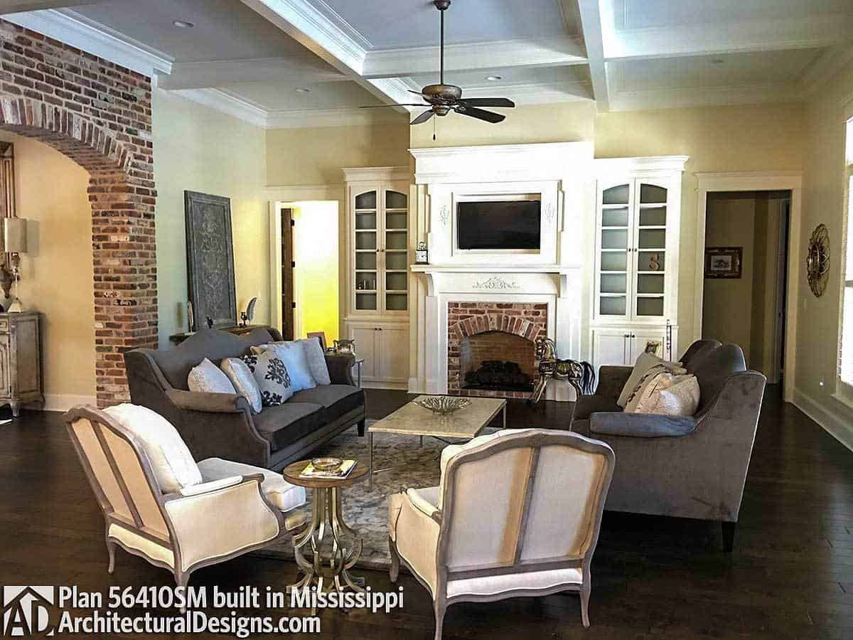 The living area has dark hardwood flooring, a coffered ceiling, and a brick fireplace matching the open archway on the side.