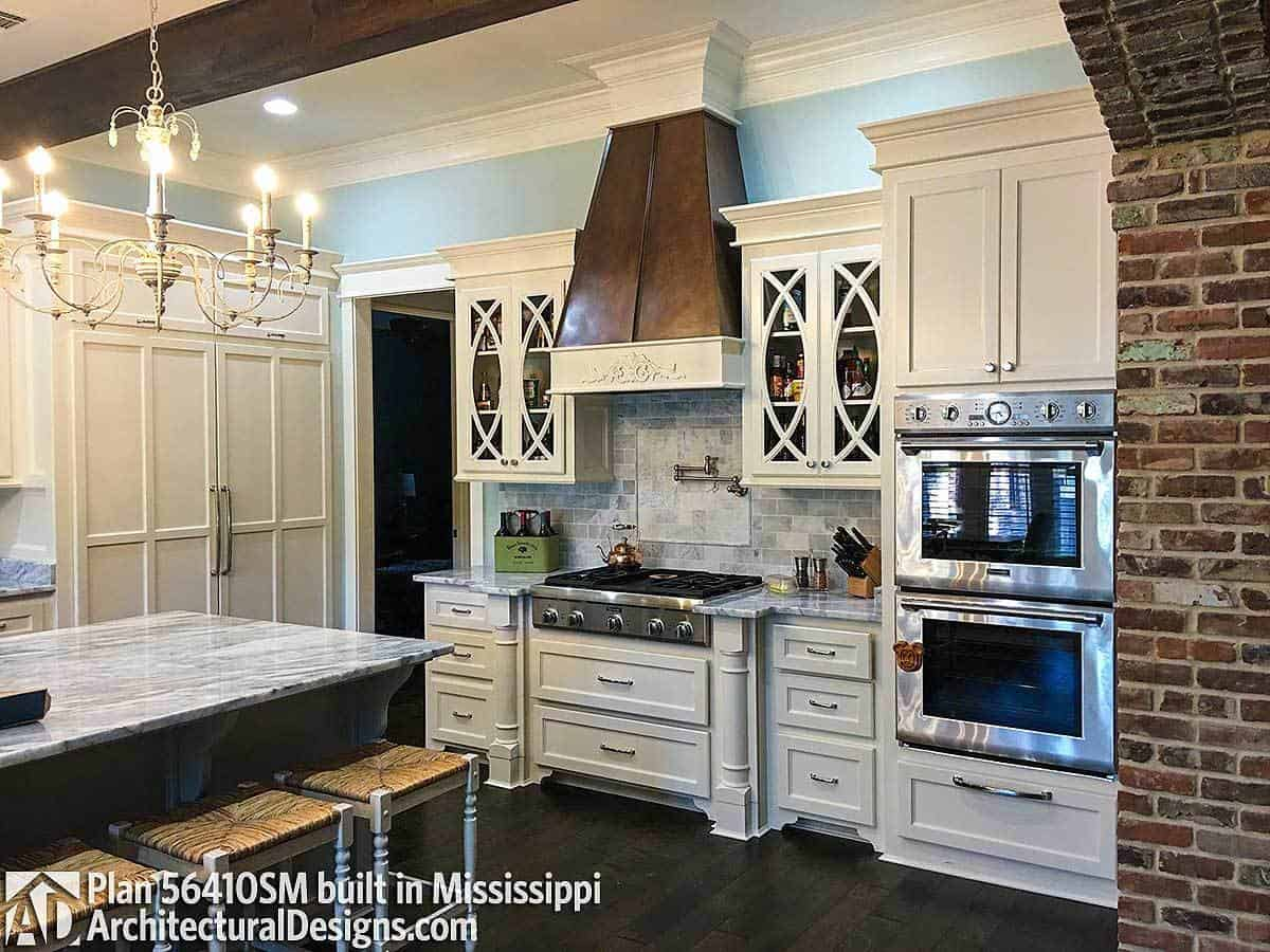 The kitchen offers white cabinetry, stainless steel appliances, and a bespoke vent hood fixed above the stone backsplash.