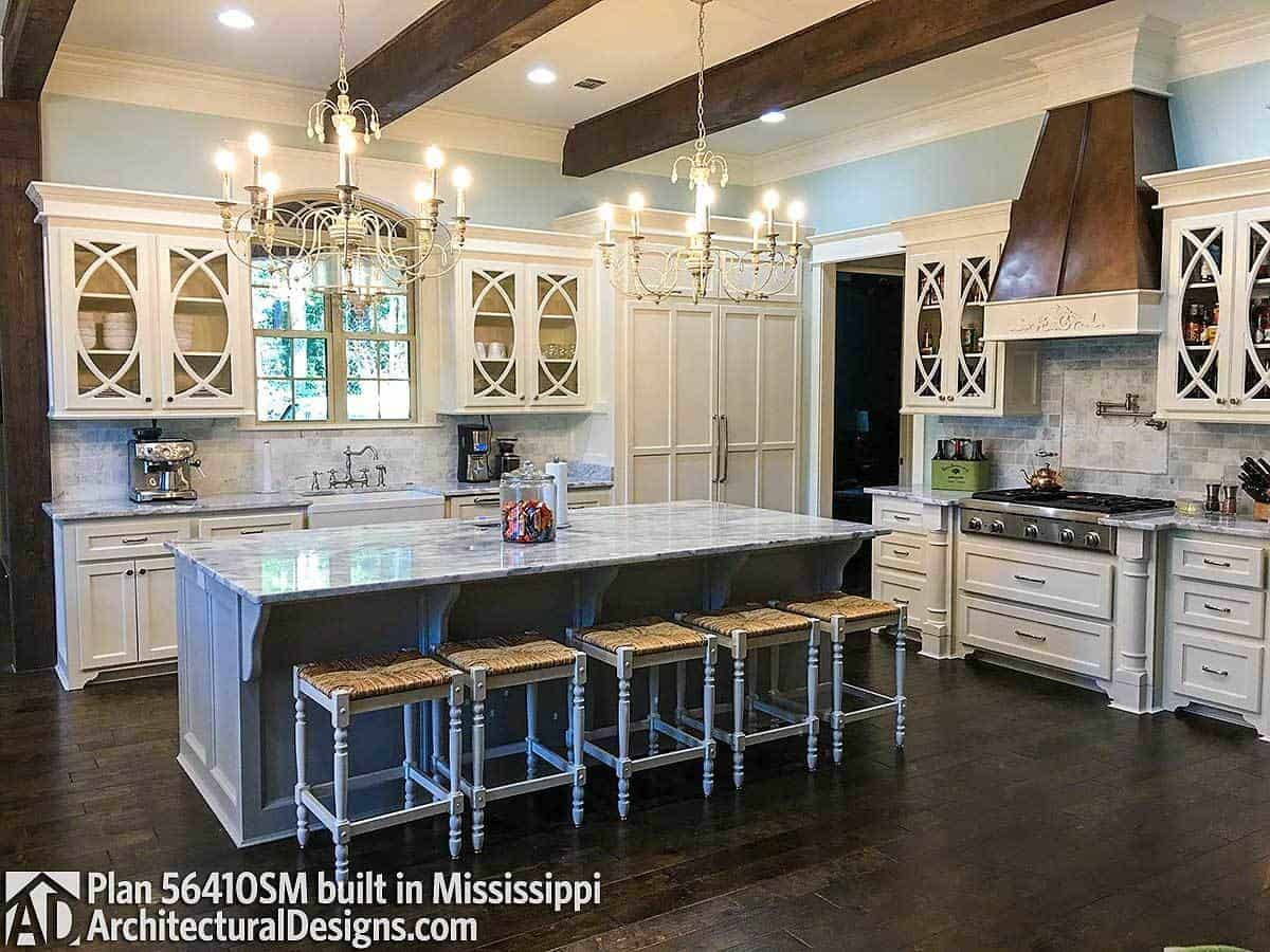 A farmhouse sink, gray center island, and candle chandeliers hanging from the beamed ceiling completed the kitchen.