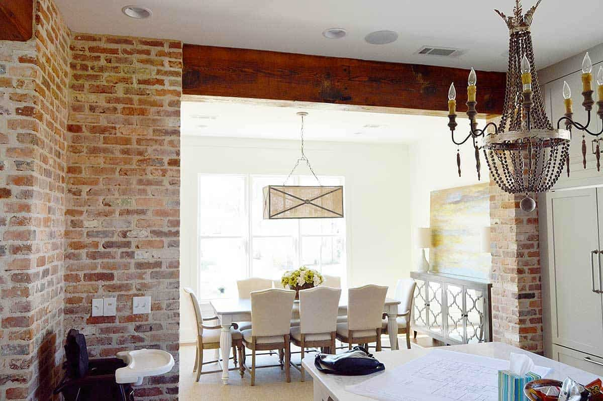The dining room offers a rectangular pendant light, white dining set, and a classy mirrored buffet topped with a sleek table lamp and abstract painting.