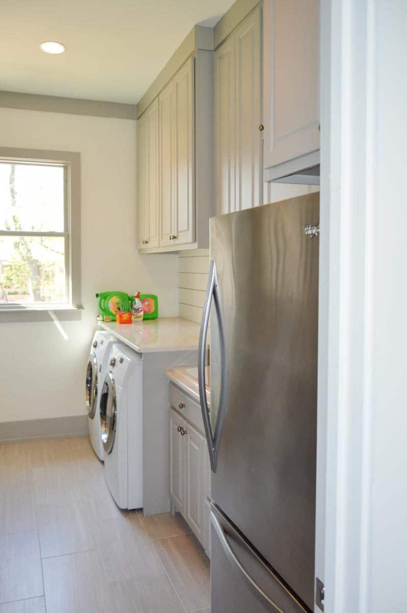 The utility room is equipped with a two-door fridge, white cabinets, and front load washing machine and dryer under the marble countertop.