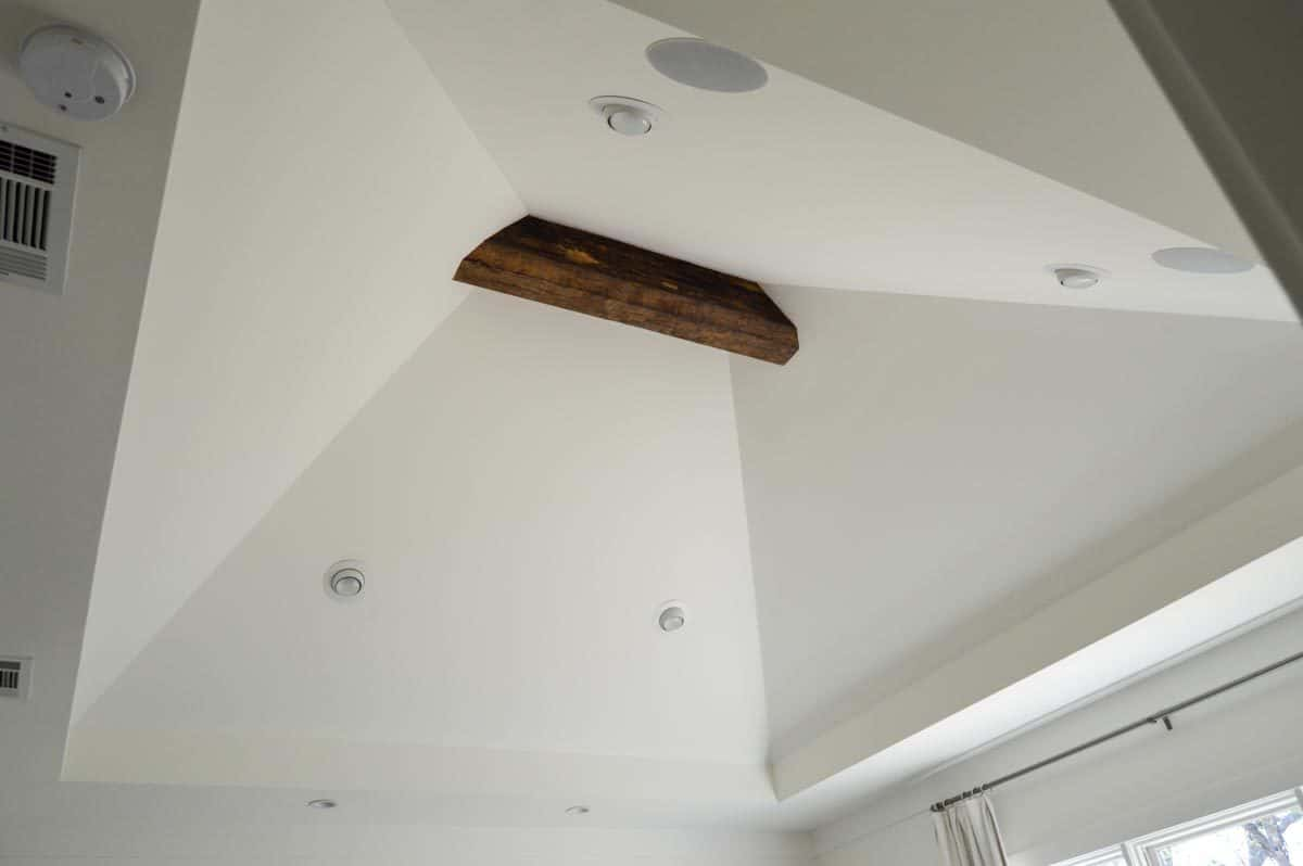 A closeup view of the vaulted tray ceiling mounted with recessed lights and a rustic wooden beam.