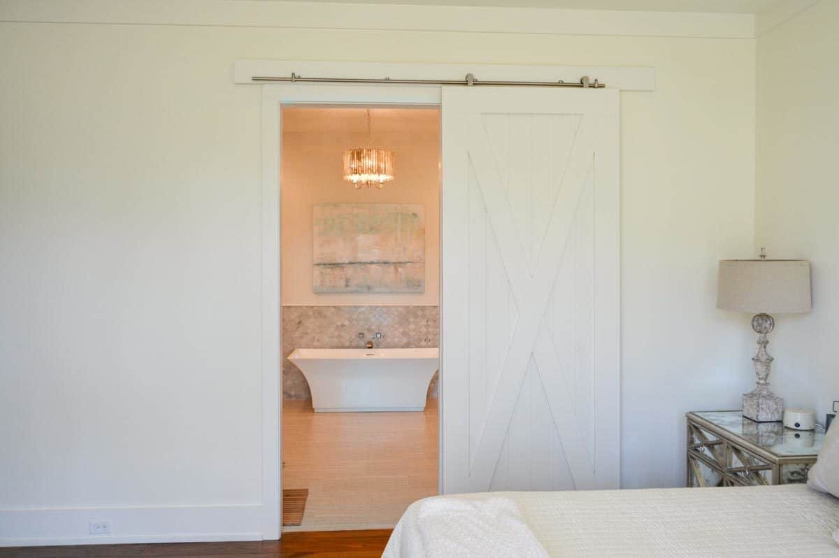 Primary bedroom with white walls and a barn door that opens to the primary bathroom.