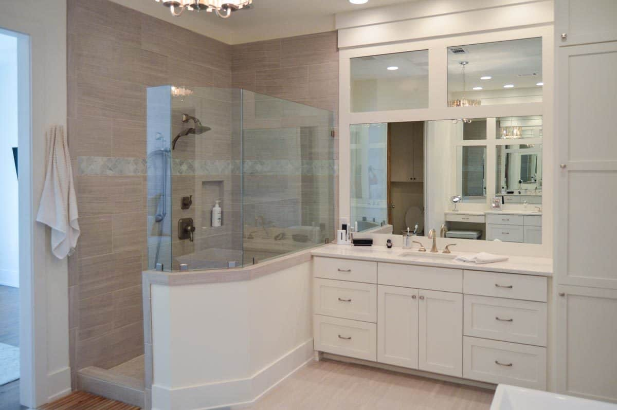 The primary bathroom offers a walk-in shower and a white sink vanity paired with a large mirror.