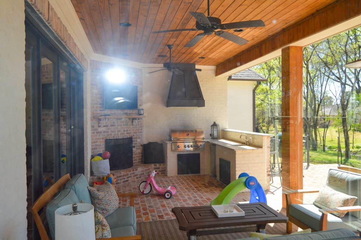 The rear covered porch is filled with outdoor living, a summer kitchen, and a corner fireplace with a TV on top.