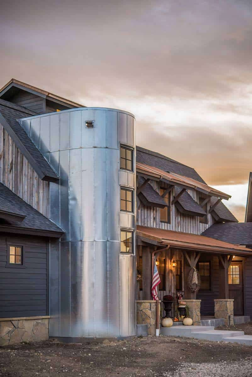 Angled view of the home's facade with a shed roof, dormers, and a curved metal-clad feature fitted with framed windows.