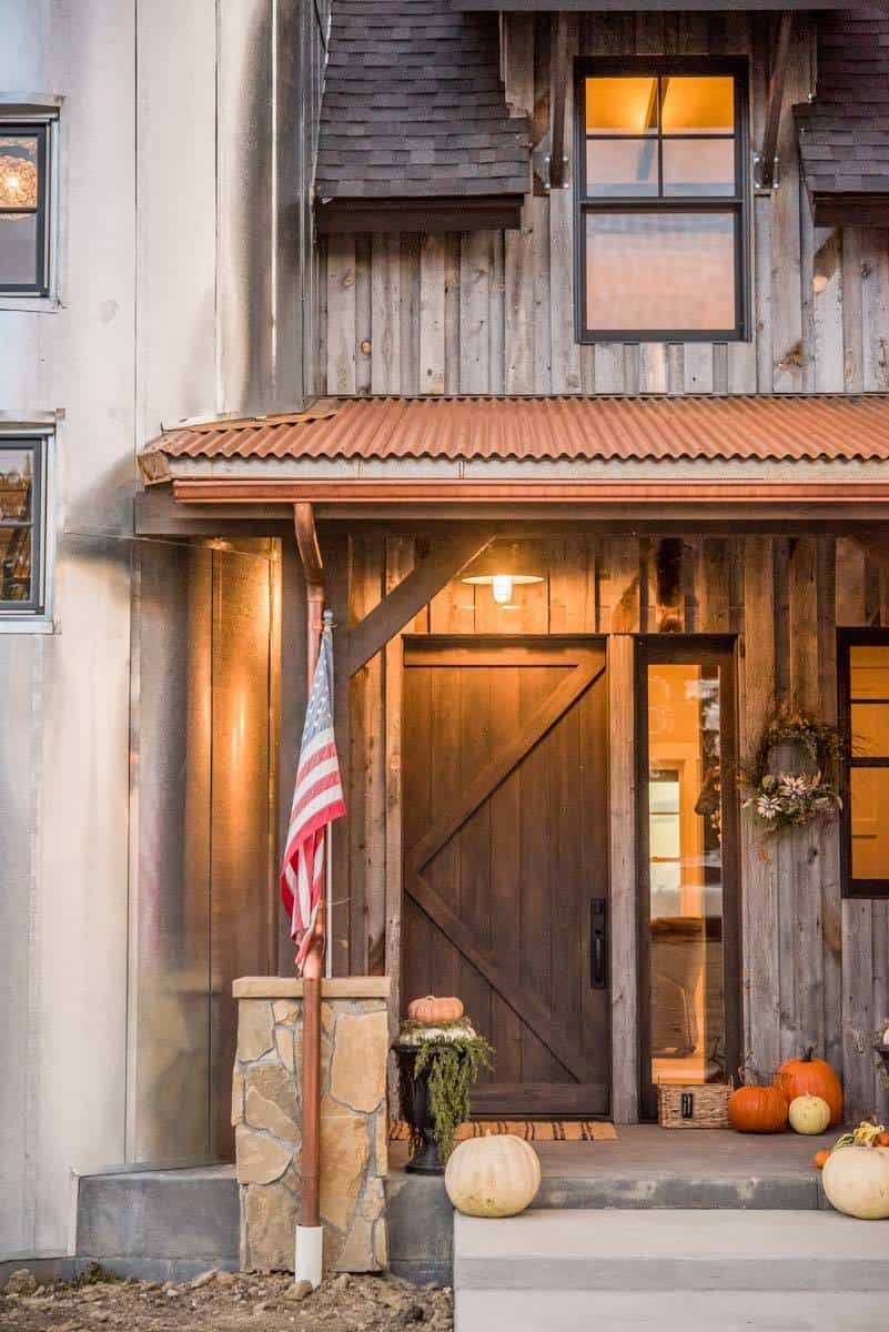 Home's entry with a rustic front door and a side glass panel.
