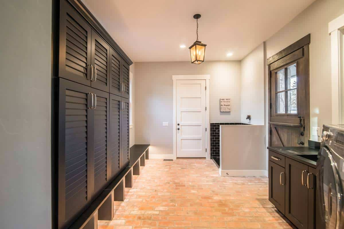 Utility room with brick flooring and regular ceiling mounted with a lantern pendant.