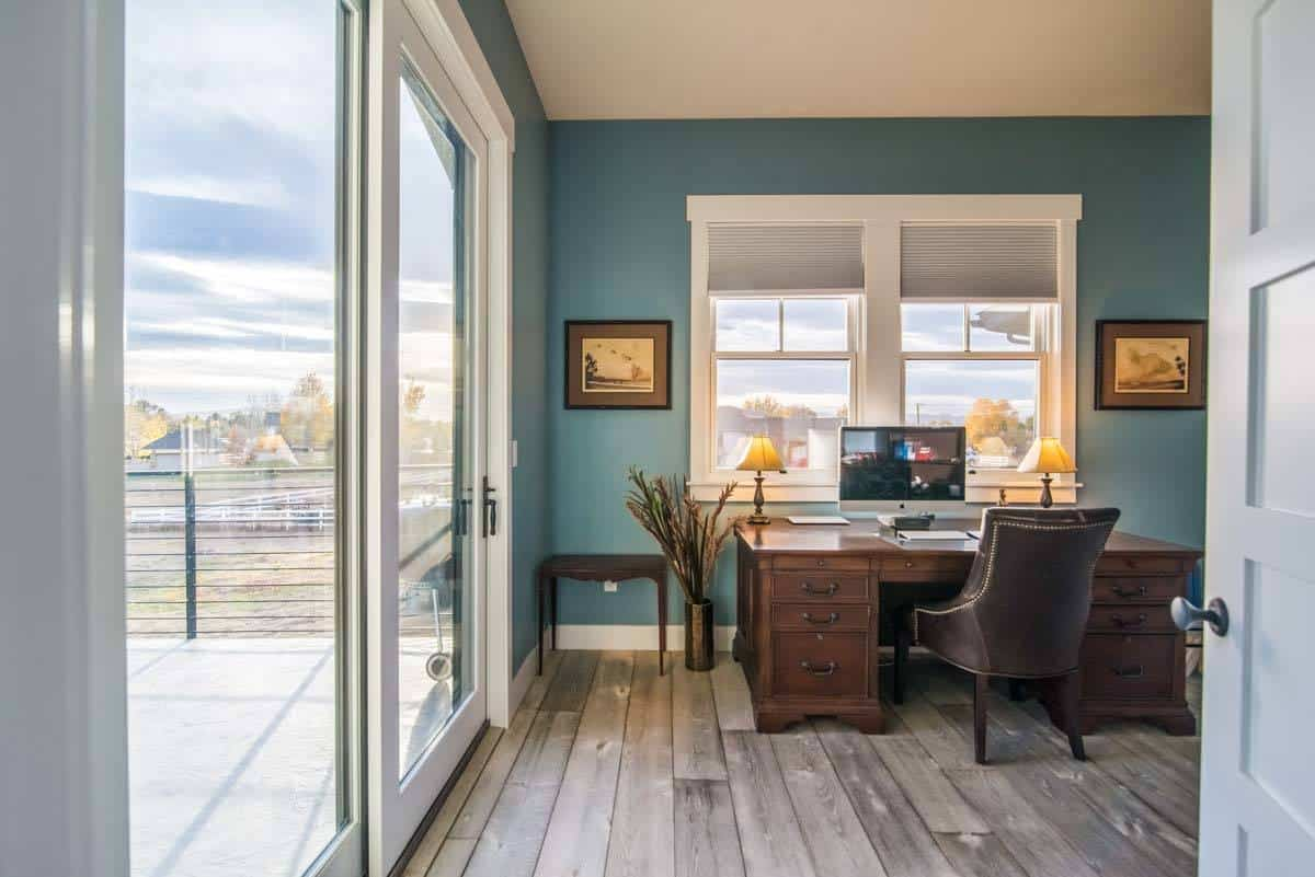 Home office with a natural hardwood flooring and gorgeous blue walls.