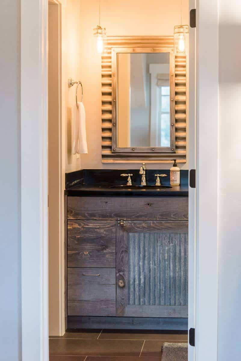 Powder room with sink vanity and a stylish mirror lit by glass pendants.
