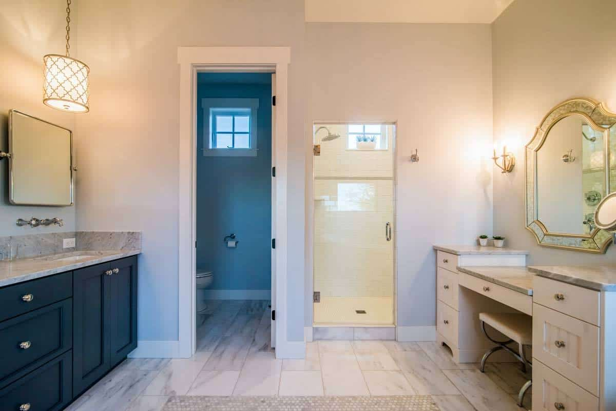 Another view of the primary bath shows the facing vanities along with the walk-in shower and water closet.