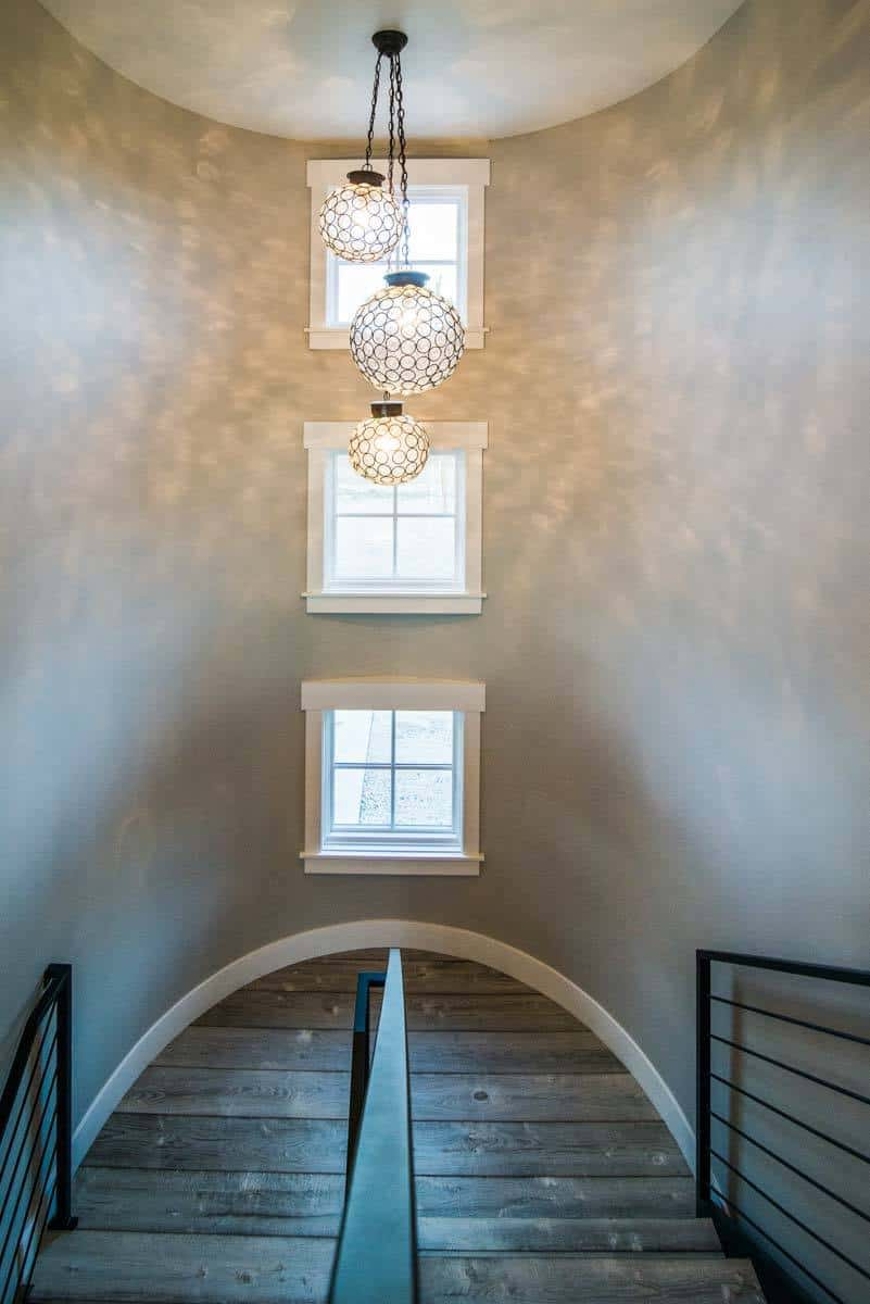 A curved staircase illuminated by three spherical glass pendants.