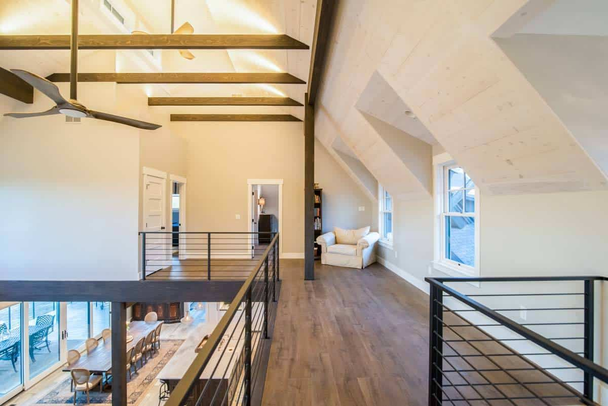 Second-floor loft with hardwood flooring and beamed ceiling.