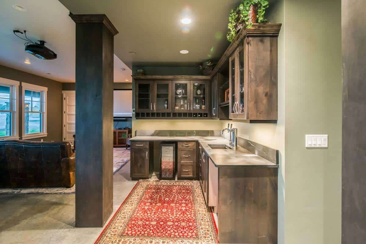 Kitchenette defined with a rustic column. It has wooden cabinetry and a red classic rug that sits on the concrete flooring.