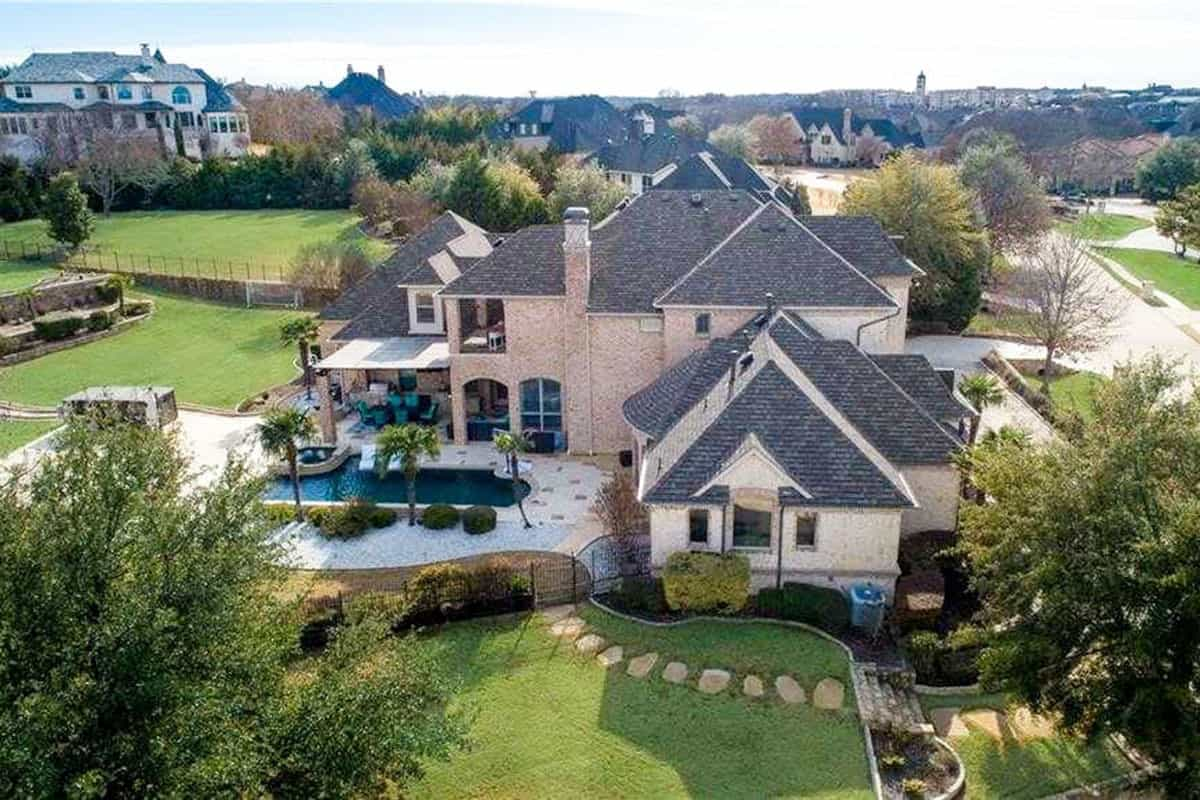 Aerial view of the two-story manor home showing the outdoor living and sparkling pool complemented with serene landscaping.