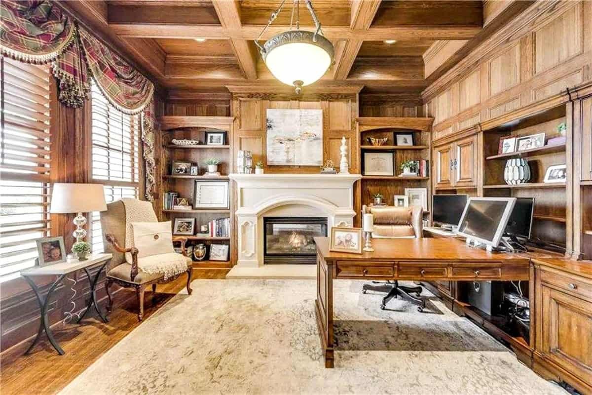 Home study with a fireplace, built-in desk, and wood-paneled walls matching with the coffered ceiling.