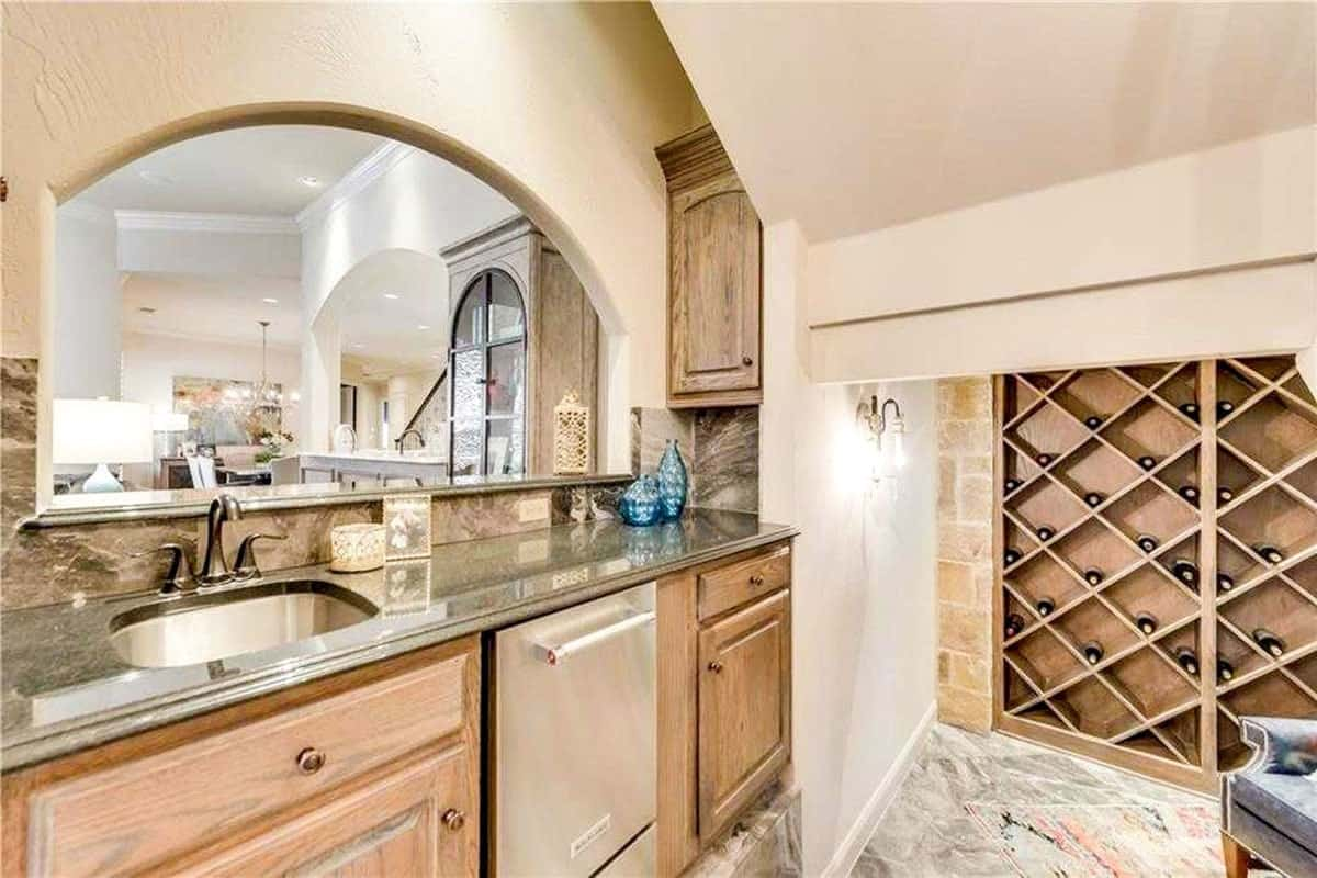 Bar with wooden cabinets, undermount sink, and an arched window overlooking the family room.