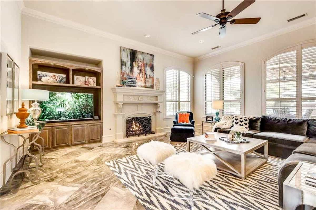 The family room offers a large TV and a fireplace enclosed in an ornate wrought iron screen.