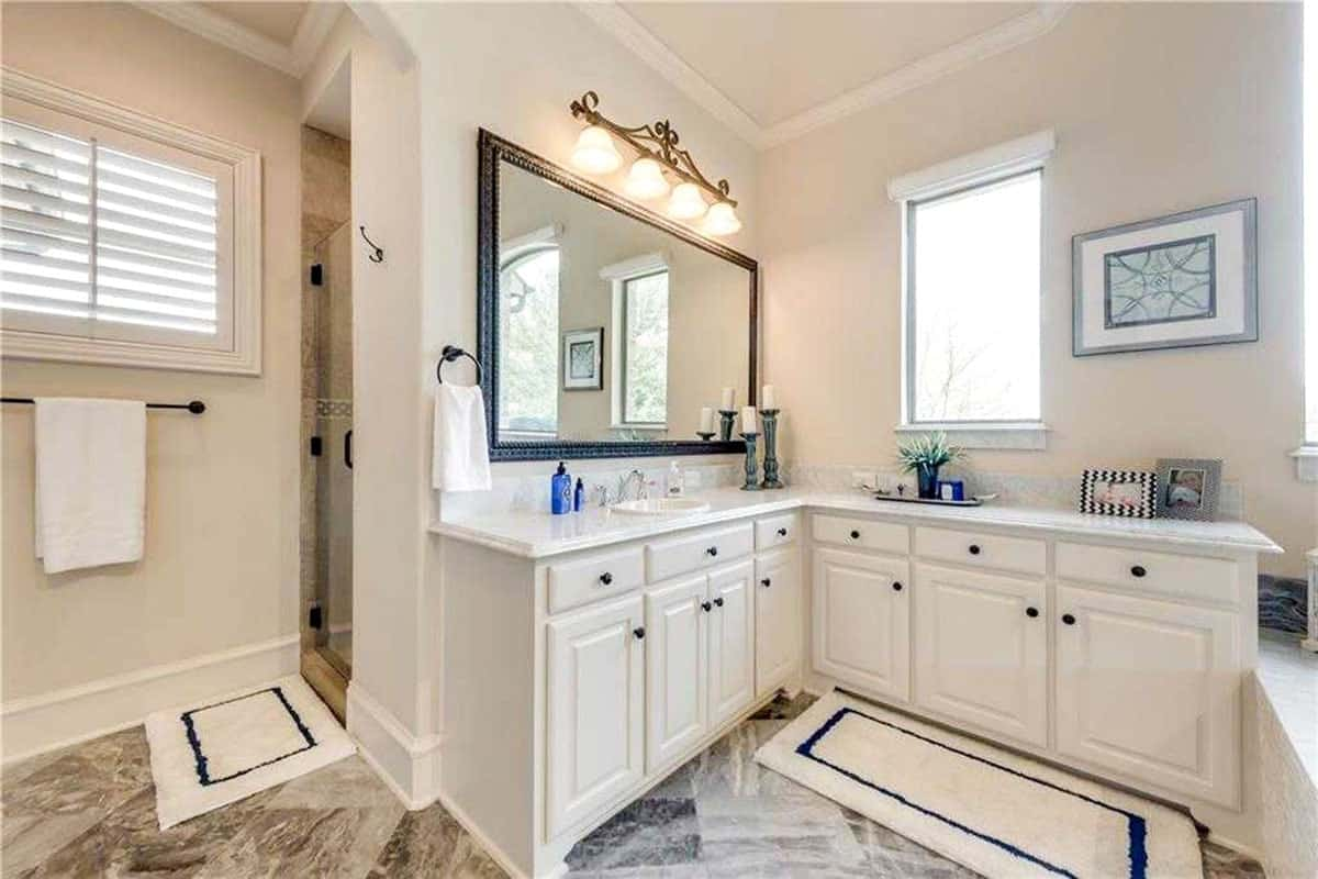The opposite side view shows another vanity and the walk-in shower complemented with bordered rugs.