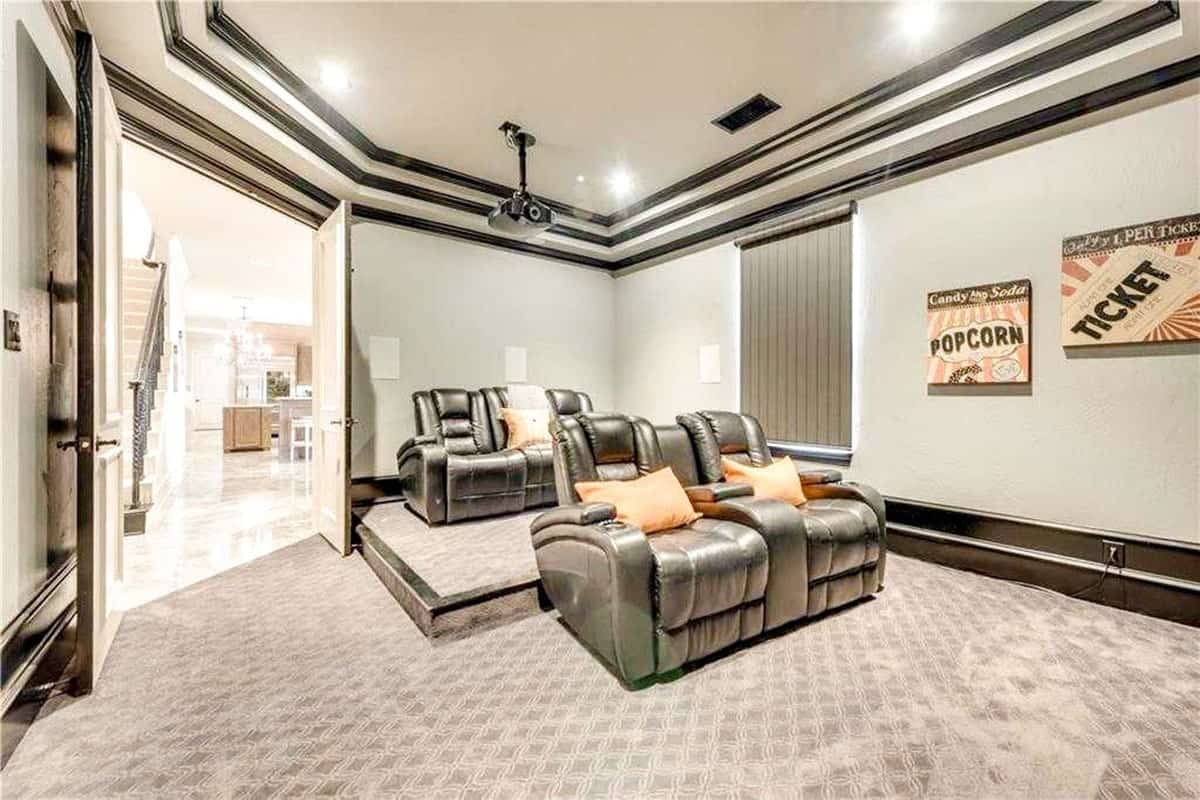 The home theater has a stunning step ceiling and black leather recliners accented with orange pillows.