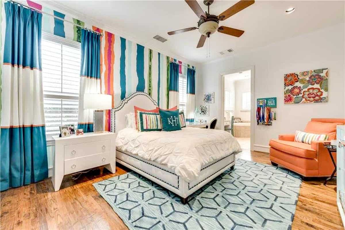 This bedroom has rich hardwood flooring and light beige walls adorned by colorful striped wallpaper and floral painting.