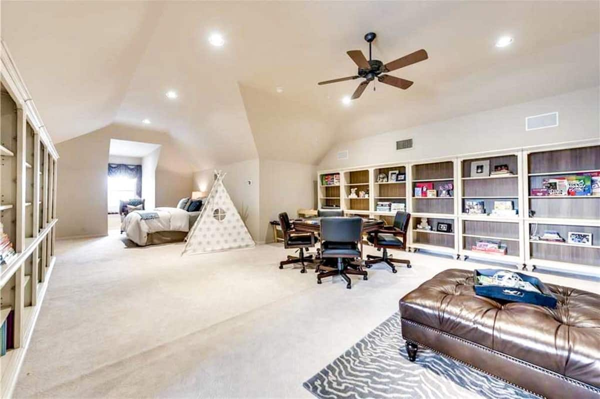 The bonus room has beige carpet flooring, vaulted ceiling, cozy seats, a bed, and lots of built-in shelves.