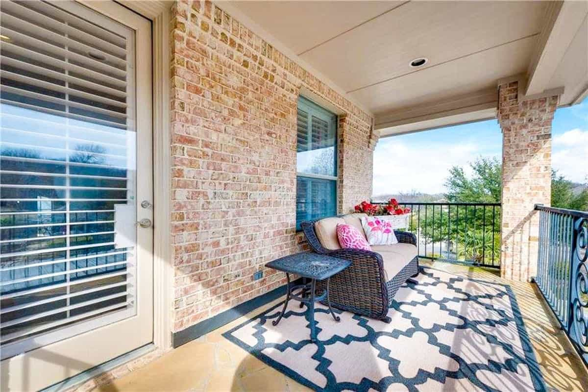 Balcony with wicker cushioned sofa and a metal side table over a large patterned rug.