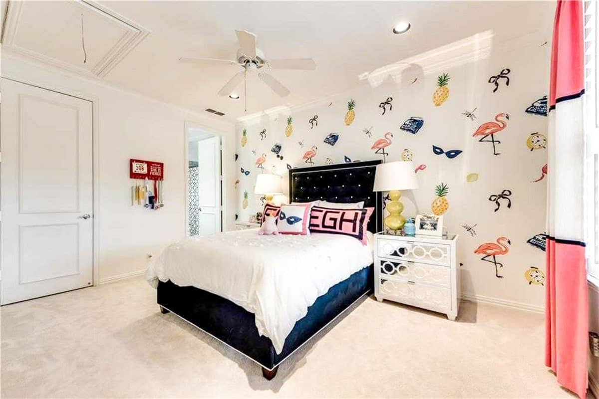 A cool patterned wallpaper sets a fun backdrop to the black tufted bed and mirrored nightstands in this kid's bedroom.