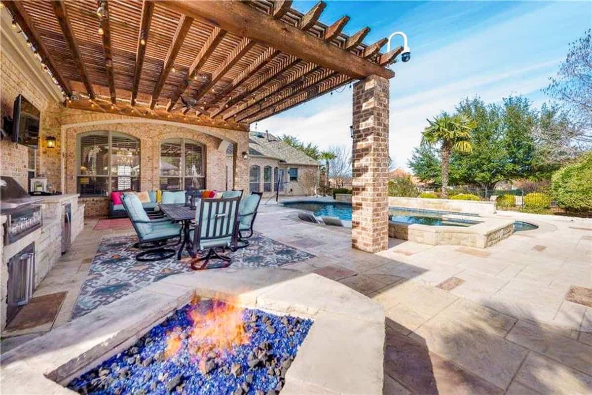 The outdoor living space filled with a fire pit, a lanai, and a tranquil swimming pool with tiled paving.