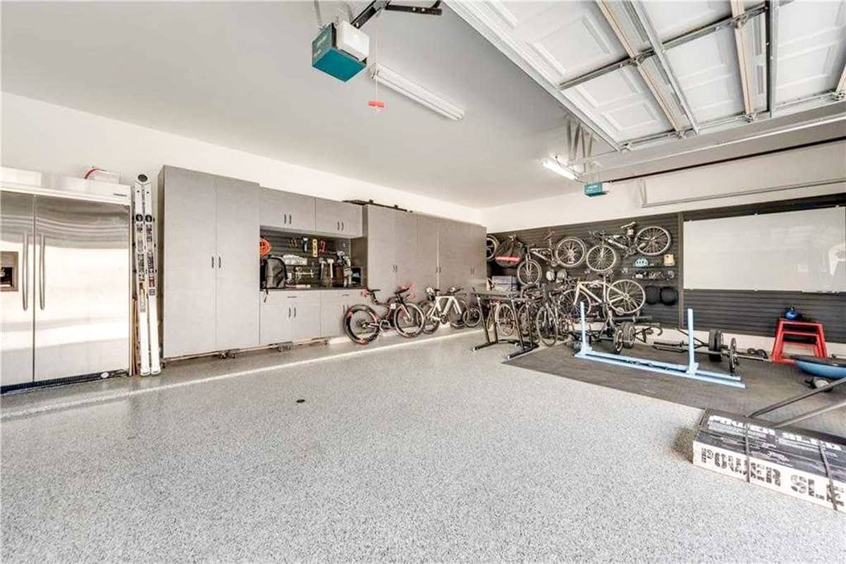 The spacious garage has a two-door fridge, gray cabinets, and lots of bikes gathered in the corner.