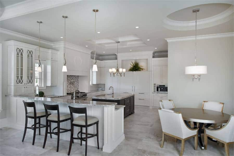The large kitchen with a breakfast nook offers a two-tier peninsula and a round dining table under a drum pendant light.