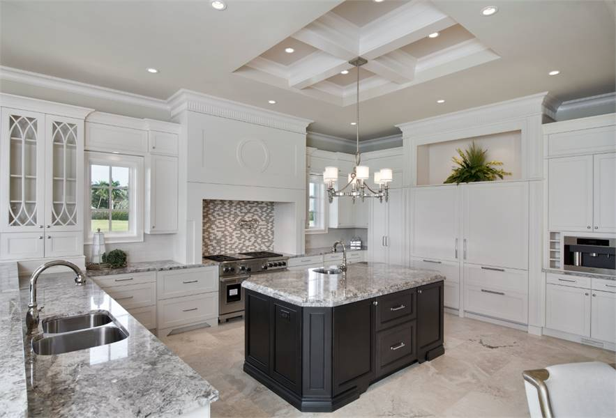 A closer look at the kitchen shows the granite top central island surrounded by pristine white cabinetry.