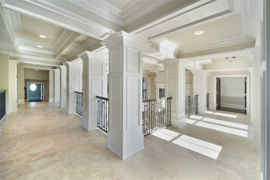 Second floor hallway lined with white wainscoted columns that support the deluxe tray ceiling.