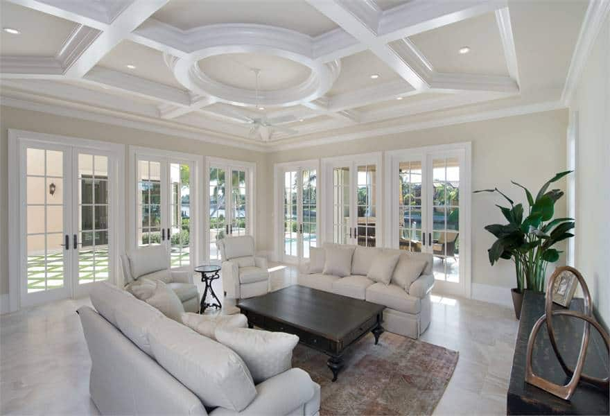 Family room with stunning tray ceiling and surrounding french doors leading out to the covered lanai.