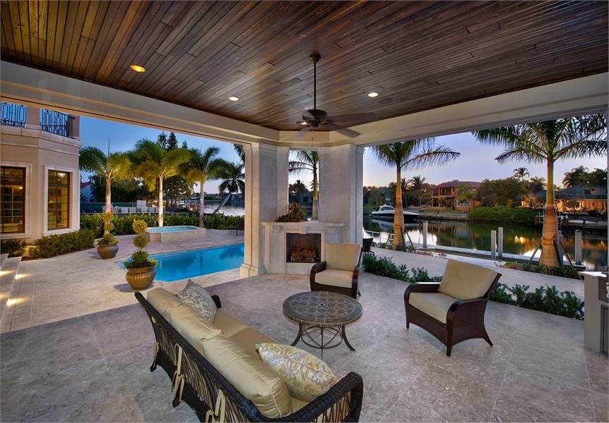 Covered lanai near the sparkling pool. It is filled with cushioned wicker seats and a round center table.