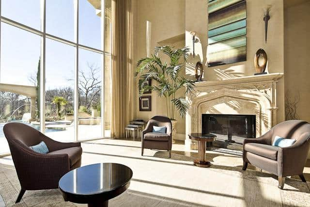 Living room with a fireplace and full-height glazing overlooking the sparkling pool.