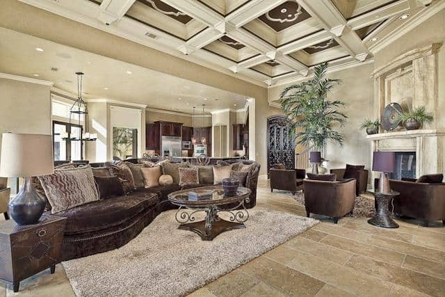 Family room with a beautiful coffered ceiling and tiled flooring topped by beige shaggy rugs.