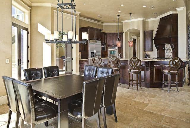 Eat-in kitchen with dark wood cabinets and ornate counter chairs sitting at the granite top peninsula bar.