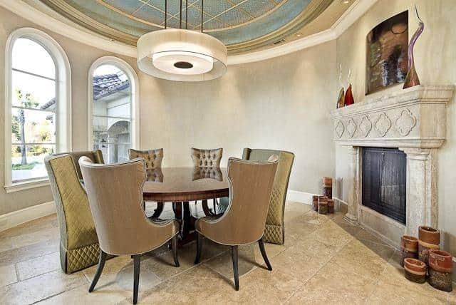 Formal dining room with arched windows, a marble fireplace and a round glass pendant hanging from the dome ceiling.