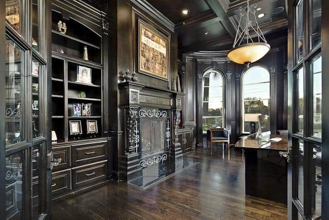 Spacious home office with a glass-enclosed fireplace and a dark wood desk under the dome pendant light.