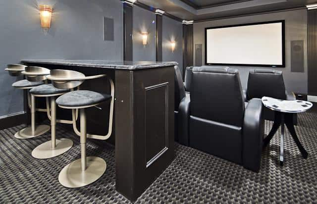 Home theater with black recliners and a peninsula bar lined with cushioned bar stools.